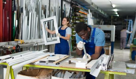 Maestro masculino está trabajando en su lugar de trabajo en el taller de ventanas.