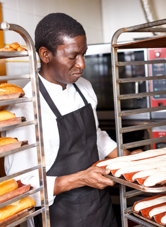 Portrait of experienced professional baker during daily work in kitchen of small bakeshop
