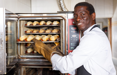 Portrait of African American baker controlling process of baking bread in professional oven at bakery