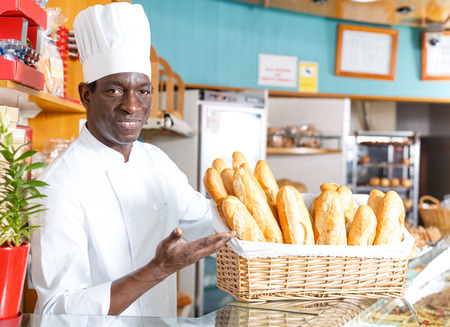Smiling African American bakery chef offering appetizing freshly baked bread and pastry in small bakery 版權商用圖片