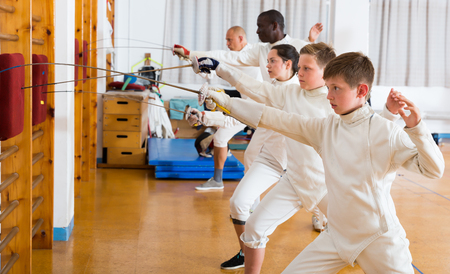 Positive mixed age group of athletes at fencing workout, training attack movements on mannequins Reklamní fotografie - 115088524