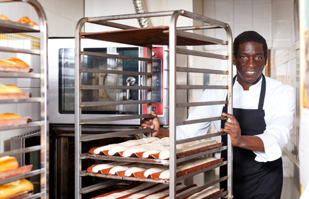 Skillful African American man working at bakery, preparing raw baguette dough for baking 版權商用圖片