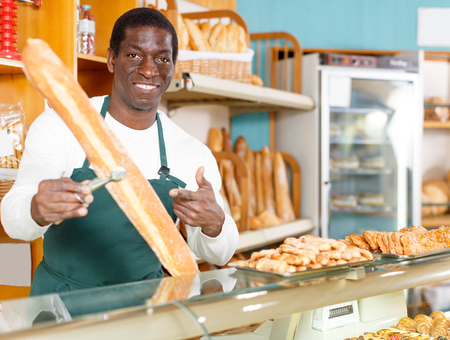 Positive baker  working behind counter in bakeshop, presenting fresh baked products