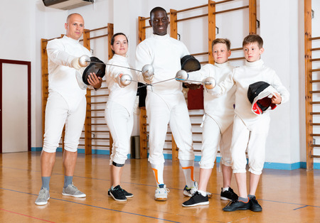 Group portrait of young  positive fencers with coaches holding rapiers in training room