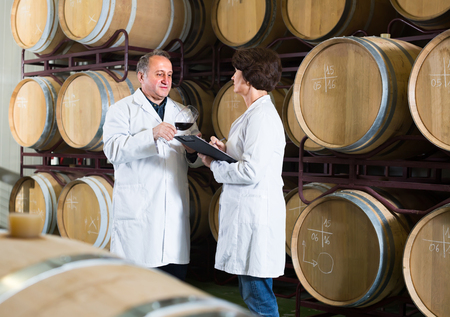 Expert and elderly wine maker estimate quality of wine and talking in cellar