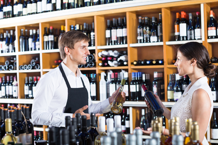 Young man seller wearing uniform helping woman customer with a bottle of wine at the wine house. Focus on both persons 免版税图像