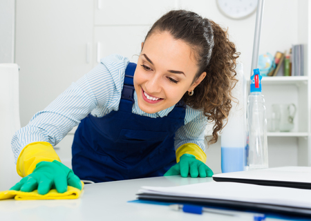 Young woman in uniform with supplies cleaning in office