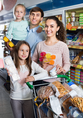 Happy smiling family with two daughters purchasing yoghurts in supermarket