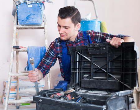 Handyman searching in his toolbox for necessary tools