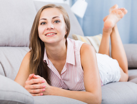 Positive young woman relaxing at home on sofa Imagens