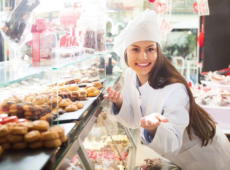 Happy brunette girl selling fine chocolates and confectionery in cafe
