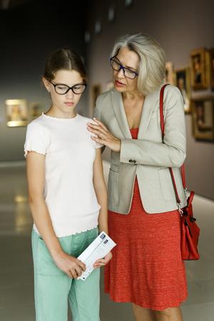 Intelligent female tutor helping tweenage girl exploring art pieces in art museum