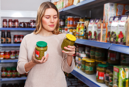 Portrait of young female choosing pickle goods in the grocery store