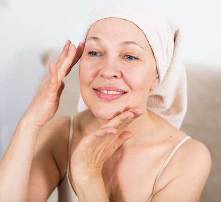 Elderly woman using face cream during beauty procedures at home Zdjęcie Seryjne