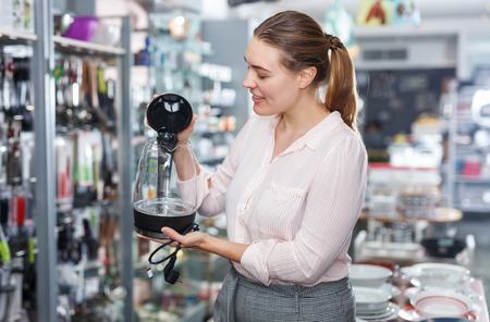 Young woman  housewife looking electric kettle in kitchen appliances section 免版税图像
