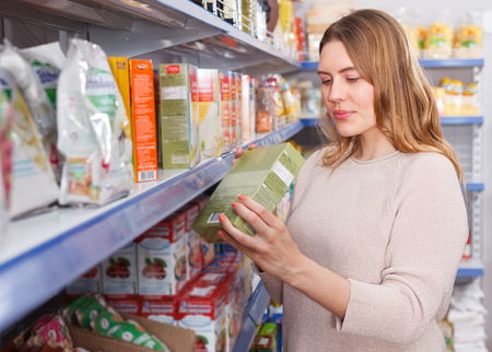 Adult girl customer choosing groats in  grocery food store