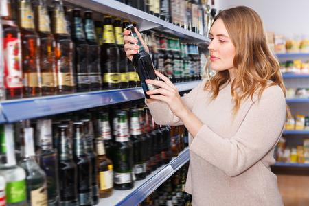 Portrait of pretty female customer buying bottle of beer in the  hypermarket