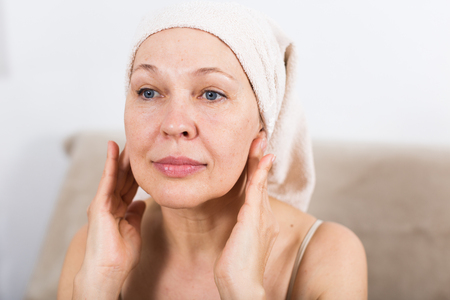 Mature woman applying face cream during beauty procedures at home Stok Fotoğraf - 115057523