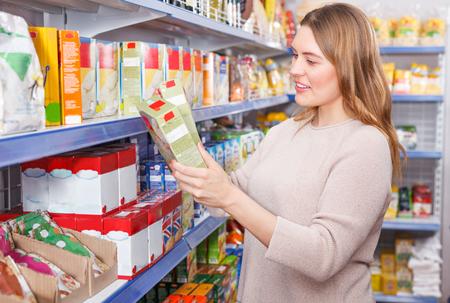 Portrait of woman customer choosing groats in grocery food shop