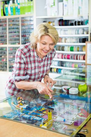 Portrait of mature cheerful woman standing next to glass showcases at shop with sewing goods