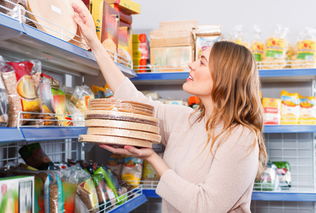 Adult smiling  woman customer choosing biscuit layers in  grocery food store Standard-Bild
