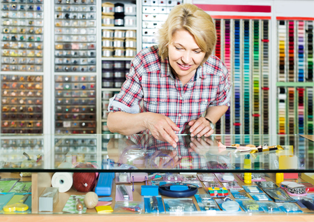 portrait of mature cheerful female cashier standing at cash desk in embroidery shop