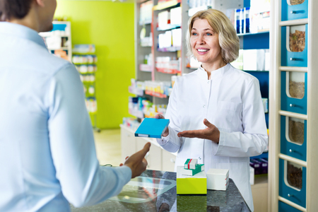 Smiling female pharmacist counseling customer about drugs usage in modern farmacy