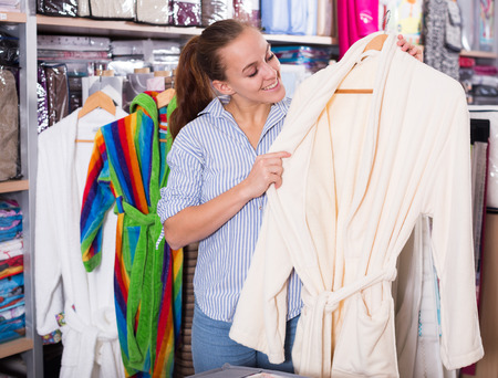 Young female customer looking through bathrobes in textile shop