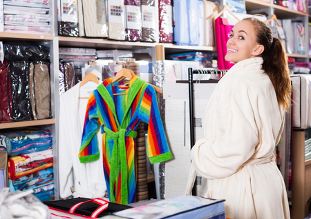 Smiling woman trying on new bathrobe in textile shop