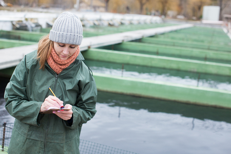Woman owner of fish farm writing results of inspection of fish tanks in notebook Stok Fotoğraf