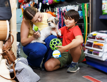 Tweenager and his young mother looking for supplies for little dog in petshop