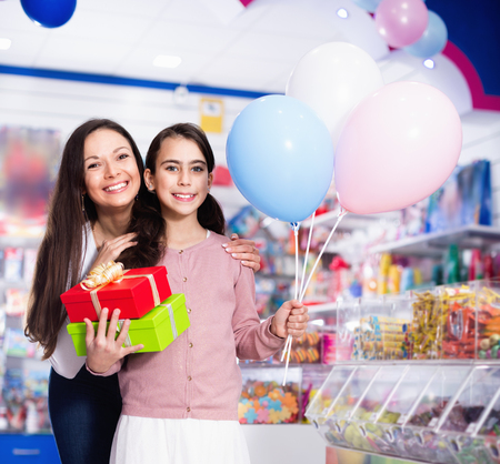 Portrait of happy cheerful positive  mother and daughter holding gifts and balloons in store Reklamní fotografie