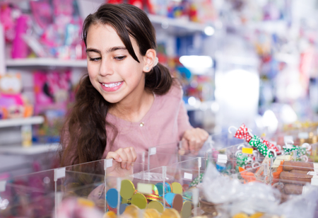 joyous schoolgirl delighted with choosing lollipop in candy store