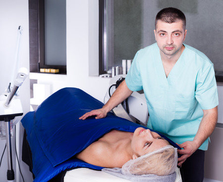 Qualified man cosmetologist with female client during hardware procedure in modern aesthetic clinic