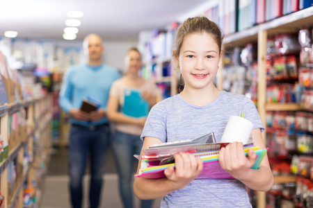 Smiling preteen girl standing with school supplies while shopping with parents in stationery shop
