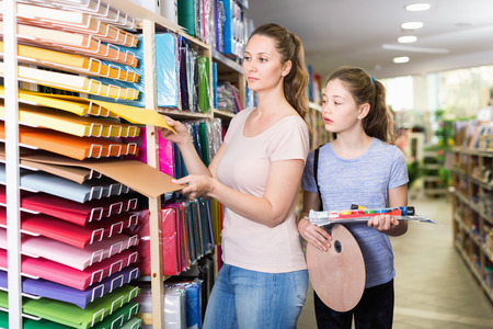 Happy positive smiling preteen girl with her young mother buying school supplies in stationery store