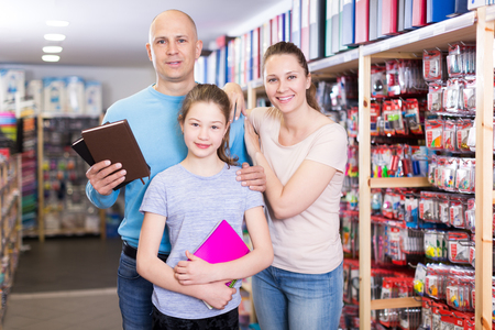 Happy parents and their preteen daughter choose notepads  in stationery store