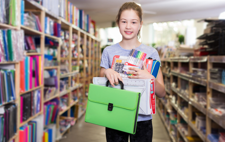 Happy girl standing with school supplies among shelves with goods in stationery store