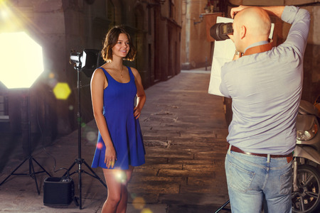 Photo shoot of young brunette model with professional photographer on old city evening street