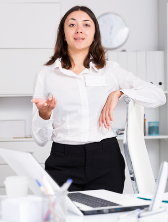 Young  woman manager standing and welcoming clients to office