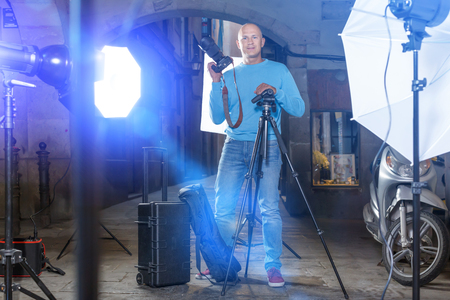 Professional photographer. Portrait of confident glad man holding camera in hands while standing among lighting equipment on city street