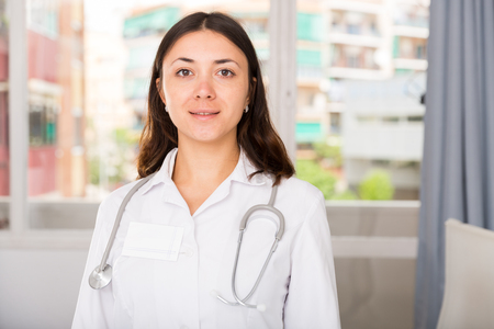 Portrait of young  woman doctor in white uniform standing in clinic's office Stock fotó