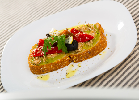 Plate with sandwich with canned tuna, guacamole, pepper, tomato, olives, arugula and Feta cheese in restaurante. Zdjęcie Seryjne
