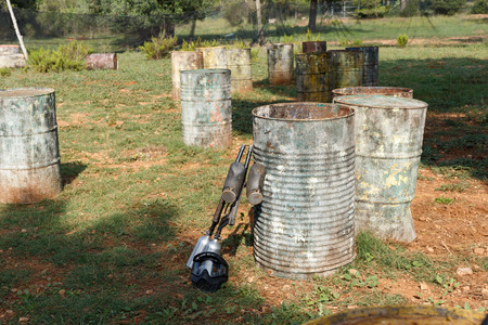 Black protective mask and marker guns lying on ground near old barrels with traces of paint on open paintball field Фото со стока - 115090985