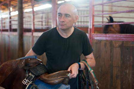 Mature man holding seats and standing at farm with horse  indoor