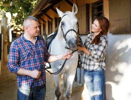 Portrait of smiling couple with white horse standing at stable outdoor Фото со стока