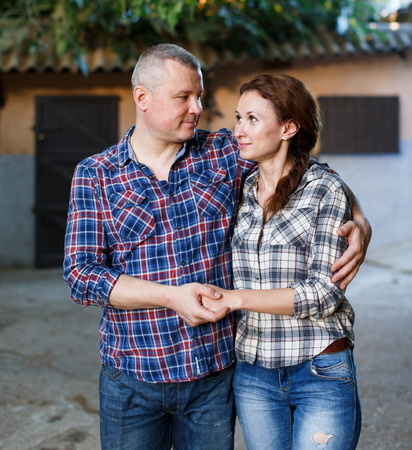 Portrait of smiling couple with girth standing at stable outdoor Фото со стока