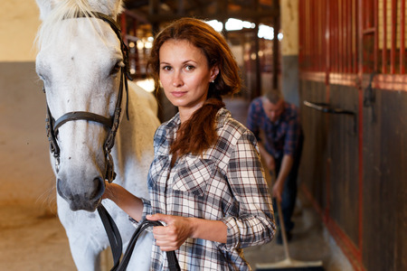 Woman farmer standing with white horse, man cleaning floor at stabling