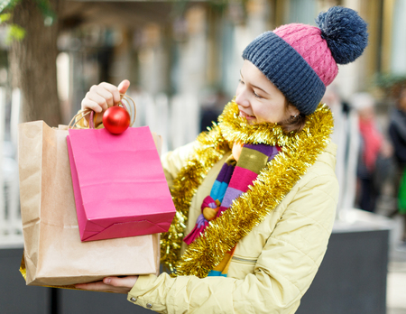 Portrait of smiling teen girl with shopping bags on festive fair before Christmas