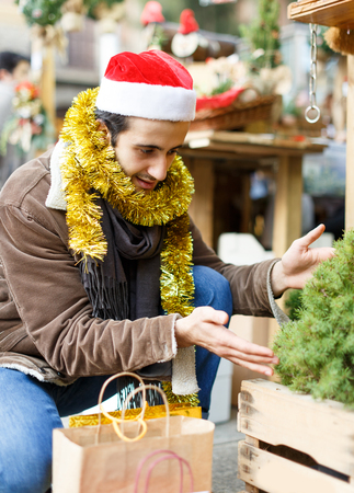Portrait of happy young man Christmas hat  with looking toys at fair outdoor